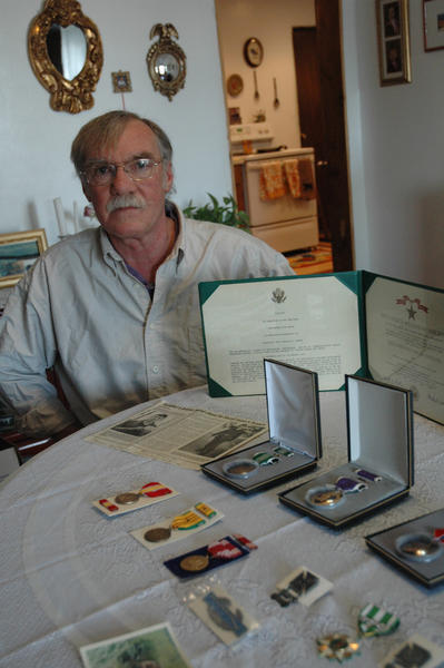 Mark Tanner of Alanson sits with medals delivered to his family more than 40 years after his brother's death in Vietnam in 1970.