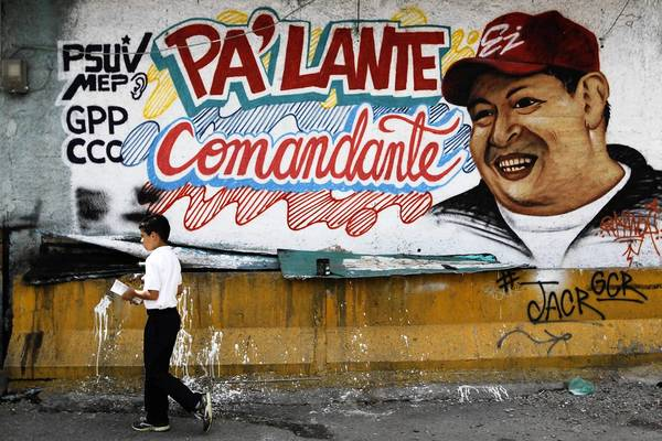 "A child walks past a mural depicting Venezuela's President Hugo Chavez in Caracas. Venezuela's opposition has accused the government of violating the constitution by proposing to delay cancer-stricken President Chavez's inauguration for a new term amid growing uncertainty over the polarized OPEC nation's political future. The mural reads, ""Go ahead commandant""."