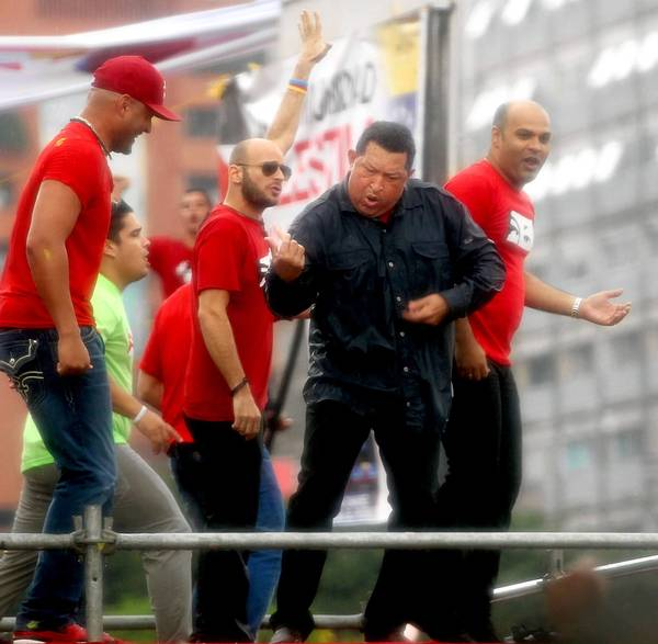 Venezuelan President Hugo Chavez plays air guitar with members of the music group Los Cadillacs for a campaign rally in 2012.