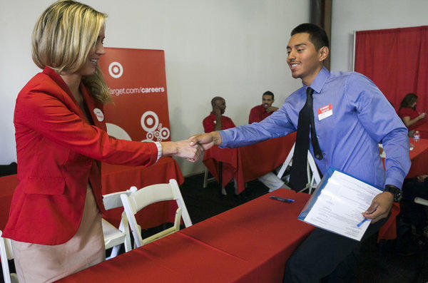 Target senior merchandiser Lauren Glasenapp welcomes prospective job candidate Daniel Martinez at a Target job fair in Los Angeles this week.