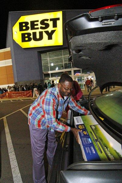 Arthur Vardaman of Madison, Miss., places a new television into the trunk of his car outside a Best Buy store in Jackson, Miss.