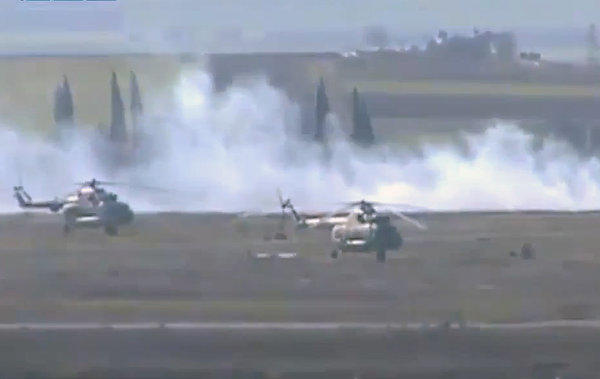 Rebel fighters battle for control of an air base in Taftanaz, Syria. The image was taken from video obtained from the Shaam News Network and authenticated by the Associated Press.