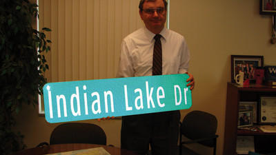Somerset County Commissioner John Vatavuk with the Indian Lake Dr. sign for the USS Somerset.
