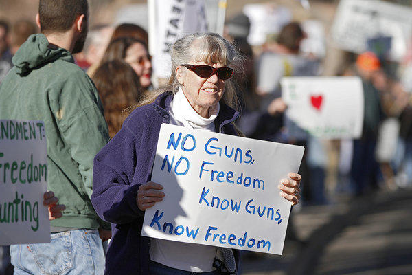 Protesters in Denver this week hold signs making a familiar, if absurd, argument: Guns guarantee freedom.