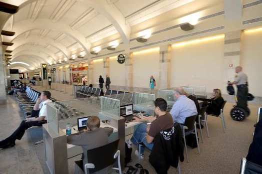Travelers at John Wayne Airport use laptops.