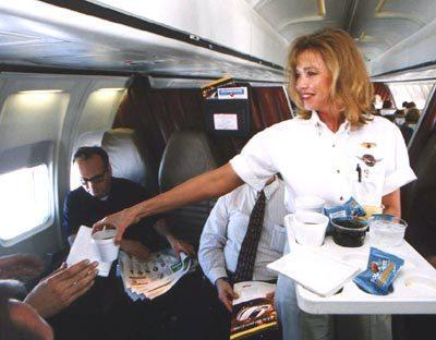 A flight attendant serves drinks.