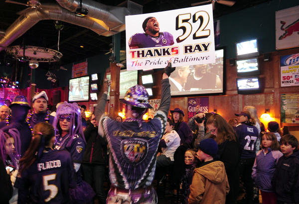 """Raven Rick"" Dixon holds his Ray Lewis sign high, getting fellow Ravens fans cheering as he walks through Looney's during last Friday night's Ravens Rally."