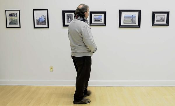 Kaplan University student Bill Shatzer of Sharpsburg looks over photographs taken by some of his classmates during a reception at the Contemporary School of the Arts Friday evening.