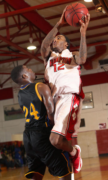 Anthony Barber of Hampton drives to the basket over Richie Staten of Phoebus during the second half Friday at Hampton.