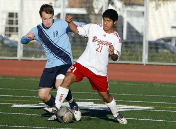 Crescenta Valley's Matt Bracht, left, and Burroughs' Chuy Nunez fight for the ball.