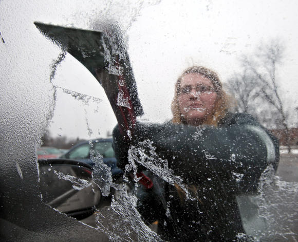 Northern State University student clears ice from vehicle