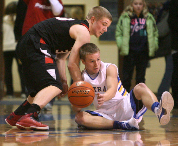 Aberdeen Central's Josh Hilgemann, center, gets control of a loose ball on the floor ahead of Brookings' Kaleb Vig during the second half of Friday night's game at the Golden Eagles Arena.