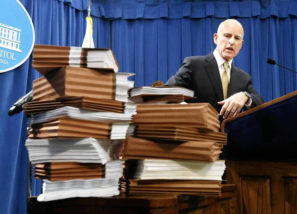 Gov. Jerry Brown gestures to a stack of reports on California prisons as he discuss his call for federal judges to return control of prisons to the state during a news conference in Sacramento on Tuesday.