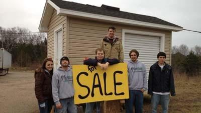 Some members of the Petoskey YouthBuild crew stand in front of a shed built as part of a fundraiser