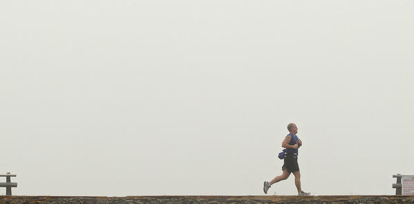 Dan Durette of Hampton runs along the seawall on Fort Monroe as heavy fog obscures the bay Saturday morning.