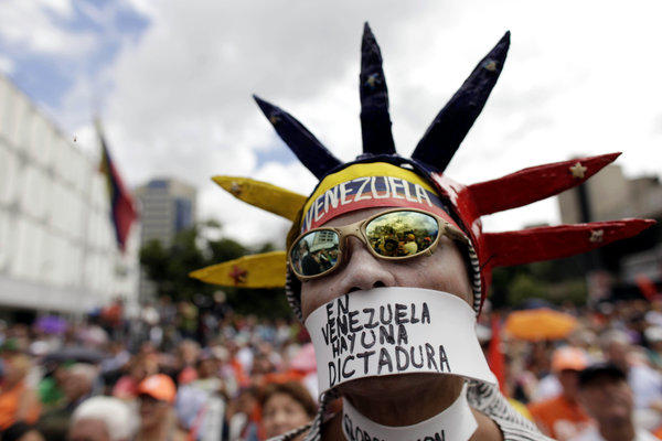 "An opponent of Venezuelan President Hugo Chavez wears a message over his mouth that reads in Spanish, ""In Venezuela there is a dictatorship,"" during a gathering Saturday in Caracas, the capital."