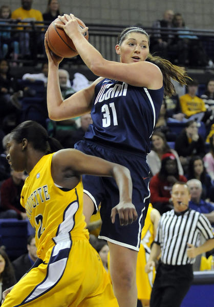 UConn center Stefanie Dolson dishes off as Marquette forward Sarina Simmons defends during the first half of their game at the Al McGuire Center in Milwaukee Saturday afternoon.