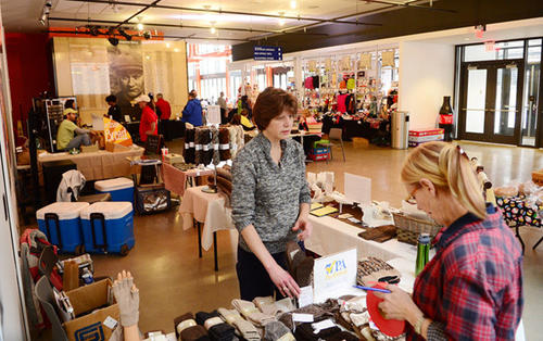 Jo Anne Givler of Germansville, center, shows goods made from the fur of the alpacas on her farm to a customer at the St. Luke's SteelStacks Farmers Market winter session. The market continues noon-4 p.m. Saturdays through March 30.