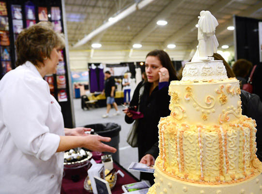 At the bridal expo at Rauch Field House Angie Dalrymple of New Tripoli, left, shows her cakes to Jacqueline Materia of Bethlehem, center, who is looking for cakes for her wedding. The expo continues from 11-4 Sunday at the Rauch Fieldhouse at Lehigh University; admission is $6; more info: www.jenksproductions.com
