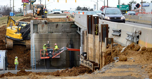 Traffic drives south on the MacArthur Road bridge over route 22 at right, while workers are at work on a crane under the bridge. Progress of construction at 7th Street/MacArthur Road exit off of Route 22 in Whitehall Township continues Friday.