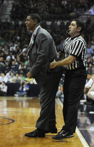 UConn coach Kevin Ollie is held back by a referee during the second half at Notre Dame.