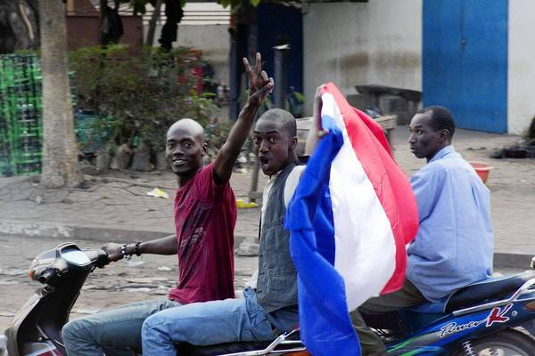 People wave a French flag in Bamako, Mali. France has sent troops and launched airstrikes to help Malian forces hold back an advance by Islamist rebels.