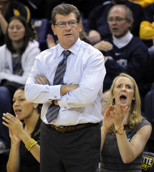 UConn coach Geno Auriemma watches as assistant coaches Marisa Moseley, left, and Shea Ralph, right, cheer on the team during the second half.