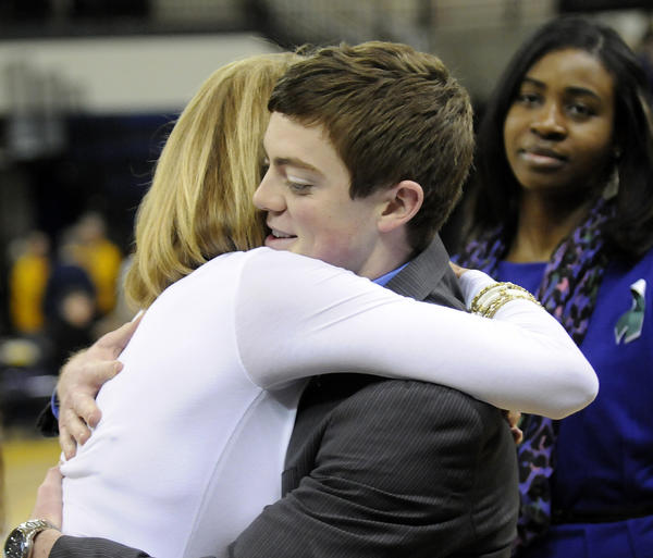 Marquette first-year assistant coach Tyler Summitt gets a hug from UConn associate head coach Chris Dailey before the start of their game at the Al McGuire Center in Milwaukee Saturday afternoon. Summitt is the son of former Tennessee women's head coach Pat Summitt.
