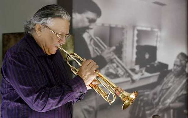 Trumpet master Arturo Sandoval at his home in Tarzana. Sandoval is standing near a portrait of himself in his 20's with Dizzy Gillespie. He's been playing trumpet for 53 years.