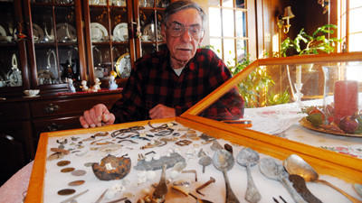 "William L. Nuzzo looking over his collection of coins, spoons, musketballs and other artifacts from a 1965 dig at the site of the old Miller's Tavern. ""They lost a lot of stuff,"" Nuzzo said. ""Here's some of it."""