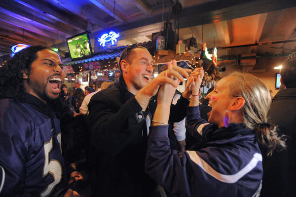 Ravens fans in Federal Hill celebrate as they watch Saturday's playoff game against the Denver Broncos.