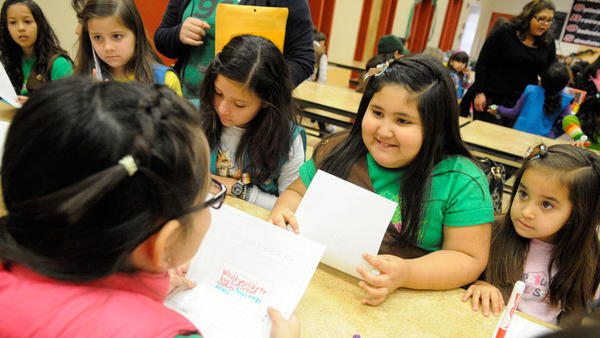 Girl Scout Celeste Yerena (second from right) practices her sales pitch with other Girl Scouts at the Cookie Kickoff on Saturday.