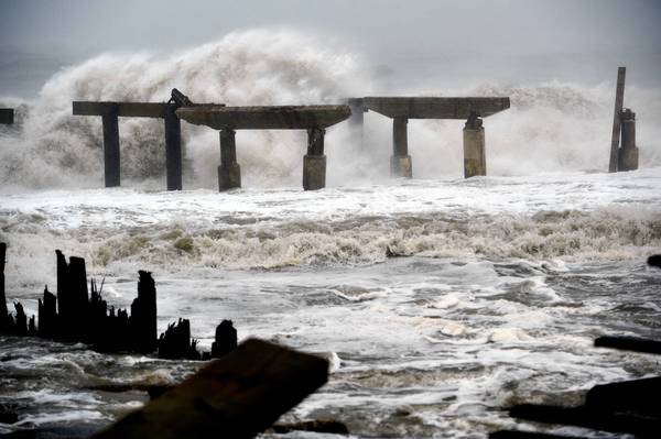 Waves crash against a previously damaged pier before landfall of Hurricane Sandy October 29, 2012 in Atlantic City, N.J.