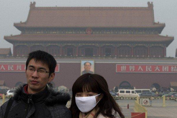 With air quality from Beijing to Guiyang at unprecedented lows, a visitor to Tiananmen Square wears a mask in the capital. Many people have refused to go outside.