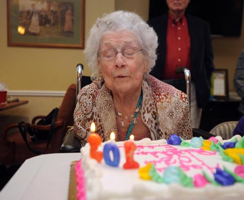 Essie Feldmann blows out the candles on her cake while celebrating her 103 birthday with her family at Emeritus.