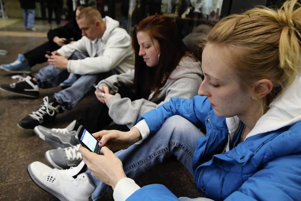 Courtney Freiberg, from right, 21, of Bridgeview; Kelcee Boosinger, 20, of Burbank; and Courtney's brother Kyle Freiberg, 20, also of Bridgeview, use their cellphones Sunday inside the Leighton Criminal Court Building in Chicago. Cook County Chief Judge Timothy Evans offered a three-month grace period on an electronics ban in the county's court buildings so that courtgoers could become familiar with the new rule.