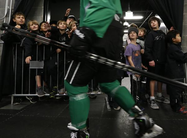 Young fans look on as LA Kings players head to the locker room after their first practice of the 2013 NHL season at the Toyota Sports Complex.