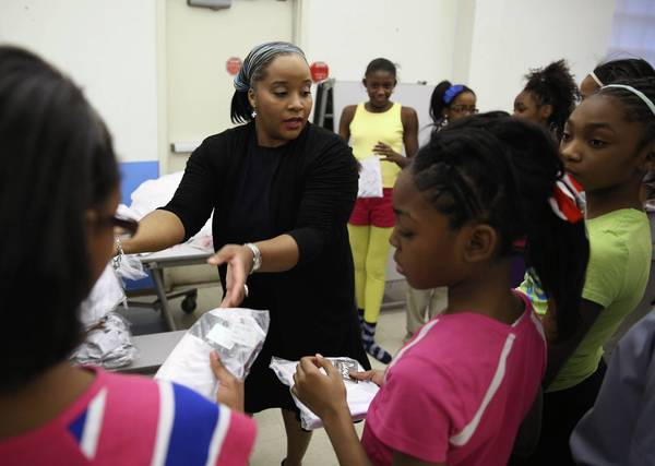 Cescily Washington helps students with their dance costumes Thursday at LEARN Charter School Network in Chicago. Washington, a former performer with the Alvin Ailey American Dance Theater, had her ballet career cut short because of abdominal surgery and now works with children who may not have been exposed to classical dance.