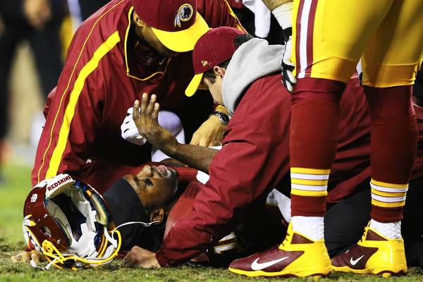 Washington Redskins quarterback Robert Griffin III is cared for last week at an NFL playoff game. Griffin played despite a leg injury. Some amateur athletes also keep playing when hurt.
