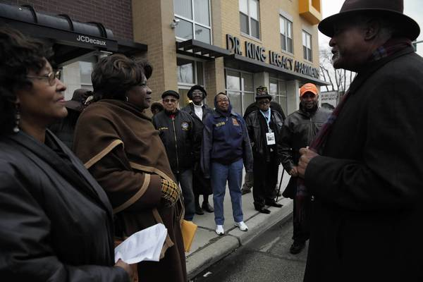 U.S. Rep. Danny Davis, right, joins Ald. Emma Mitts, 37th, left, and Metropolitan Water Reclamation District Commissioner Barbara McGowan in front of the Dr. King Legacy Apartments during a Sunday bus tour of West Side sites tied to Dr. Martin Luther King Jr.
