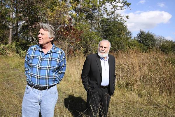 Coy Koontz Jr., left, and his attorney Alan E. DeSerio tour the land in November.