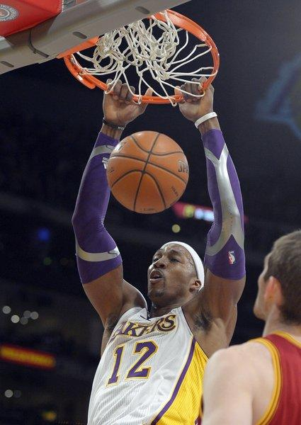 Lakers center Dwight Howard dunks as Cleveland Cavaliers center Tyler Zeller watches.