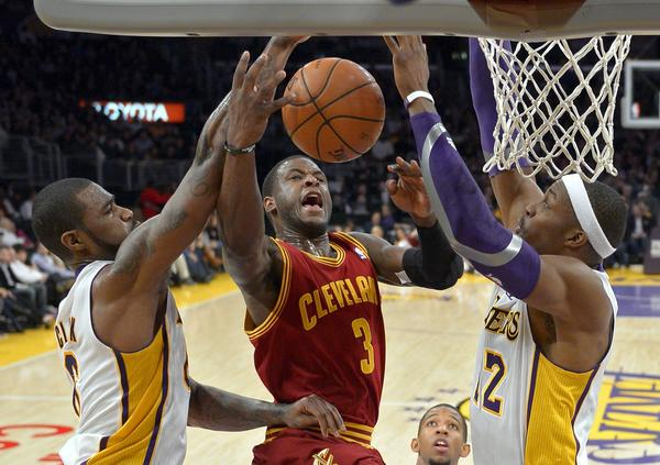 Cavaliers guard Dion Waiters, center, goes up for a shot as Lakers' Earl Clark and Dwight Howard defend.