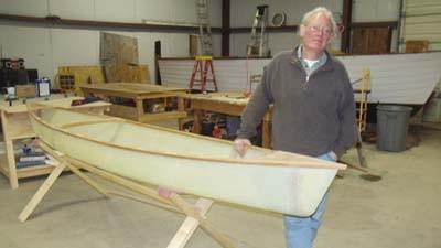 Dave Lesh, founder and executive director of the Michigan School of Boat Building and Marine Technology, stands next to a canoe built by students in a high-school level program in 2012.