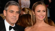 Stacy Keibler proved she's still very much with George Clooney, walking the red carpet arm in arm with him Sunday evening at the 2013 Golden Globe Awards.