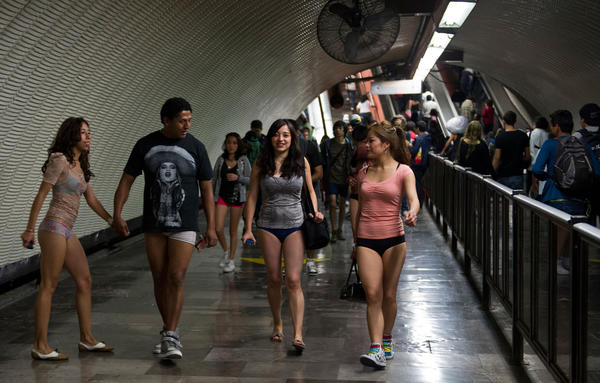 People walk through a subway station during the worldwide 'No Pants Subway Ride' event  in Mexico City on January 13, 2013.