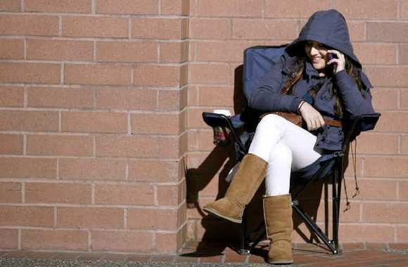A young girl took a seat in the warm sun with a hot drink and her cell phone on a cold and windy morning on Colorado Blvd. near Central Ave., outside the Glendale Galleria Target, in Glendale on Friday, January 11, 2013.