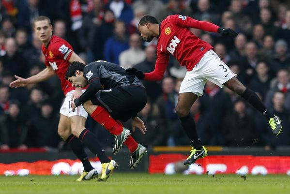 Manchester United's Patrice Evra (R) fouls Liverpool's Luis Suarez during their English Premier League soccer match at Old Trafford in Manchester, northern England, January 13, 2013.