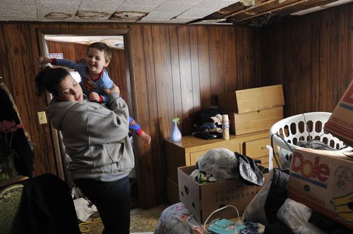 Jenna Howard picks up her son, Sebastian Byrd, 3, in the room which was her bedroom until part of the ceiling fell when Superstorm Sandy hit the area. Now Howard and her three sons stay in the living room, the only room with electricity and heat.