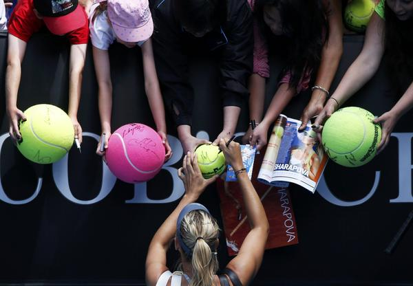 Maria Sharapova of Russia signs autographs after defeating compatriot Olga Puchkova in their women's singles match at the Australian Open tennis tournament in Melbourne, January 14, 2013.